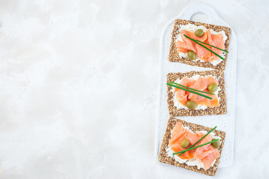 Sandwich with smoked salmon and cream cheese on thin multi seed  crispbread, garnished with green onion and olives, horizontal, top view, copy space