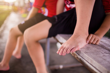 Sports injury. Youth soccer player in ankle pain. Doctor perform checking and first aid at knee trauma. Soccer player sitting because ankle pain from playing.