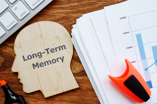 Writing note showing Long-Term Memory. The text is written on a head-shaped plaque. Papers with graphs, keyboard, notebook, a pen are on the photo too.