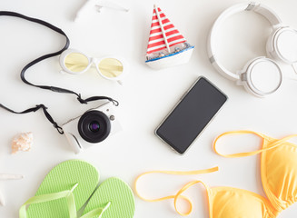 top view travel concept with digital camera and Outfit of traveler on white wooden background, Tourist essentials, vintage tone effect