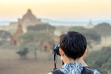 Back wiew of tourists admire and take photography while the sun sets at the ancient pagoda temples in the asian historic heritage city Bagan, Myanmar Wall mural