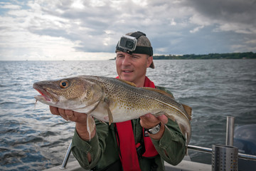 Happy angler with cod fishing trophy
