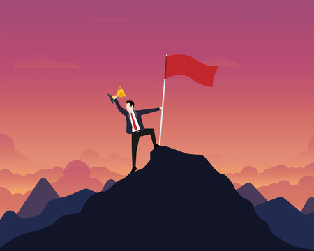 Businessman holding up a gold trophy cup with success flag on top of mountain