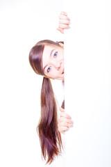 Teenage woman / girl hiding behind a board