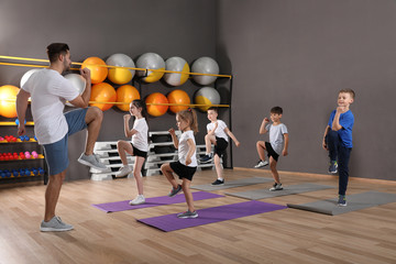 Cute little children and trainer doing physical exercise in school gym. Healthy lifestyle