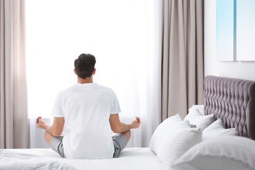 Man meditating on bed at home. Zen concept Wall mural