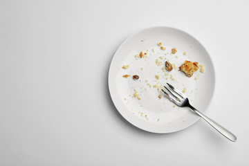 Dirty plate with food leftovers and fork on white background, top view Wall mural