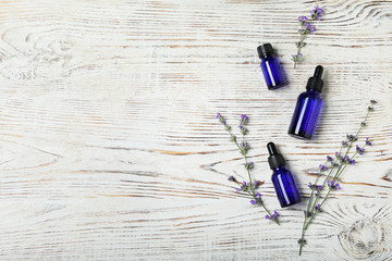 Bottles of essential oil and lavender flowers on white wooden background, flat lay. Space for text