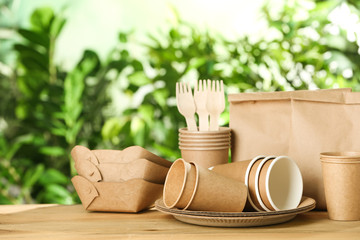 Paper dishware on wooden table against blurred background, space for text