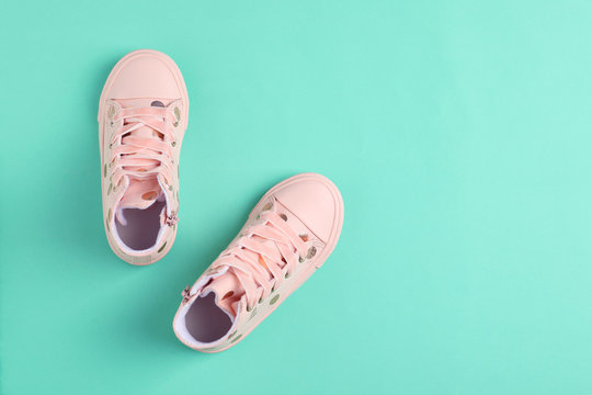 Pair of stylish child shoes on turquoise background, flat lay. Space for text