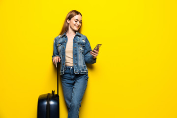 Tourist woman with suitcase in summer casual clothes with phone isolated on yellow background