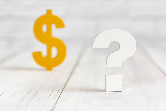 Question mark with dollar sign on white wood table over white brick background with copy space.