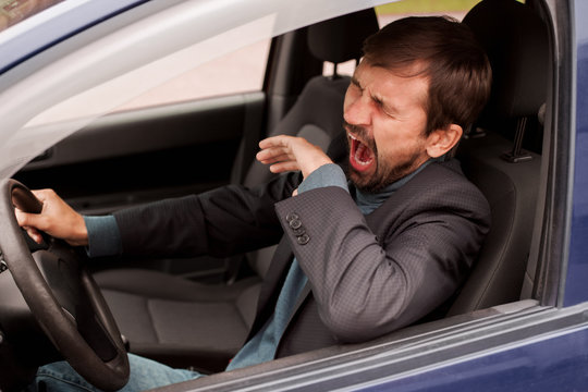 Tired man yawning while driving his car