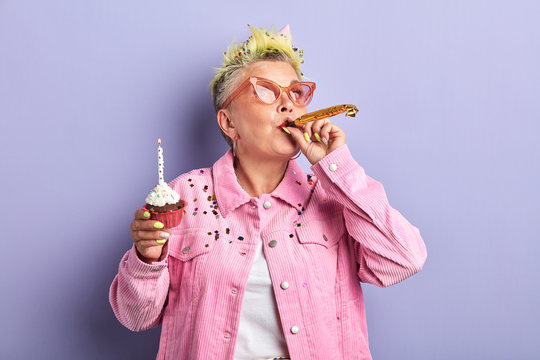 Happy pretty old woman wearing sunglases and pink fashion jacket cheering and celebrating birthday. New year and celebrate concept.isolated violet background, lifestyle