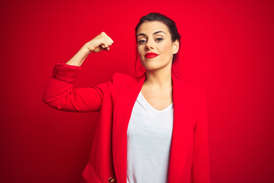 Young beautiful business woman standing over red isolated background Strong person showing arm muscle, confident and proud of power