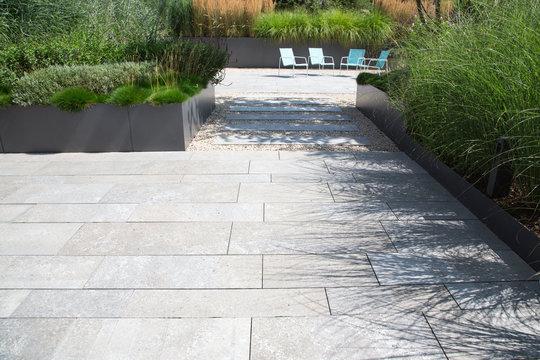 Moderne Garten- und Terrassengestaltung im Materialmix: Terrasse und Gehweg aus Steinplatten umgeben von Schotter und Metall Pflanzgefäßen mit Grünpflanzen