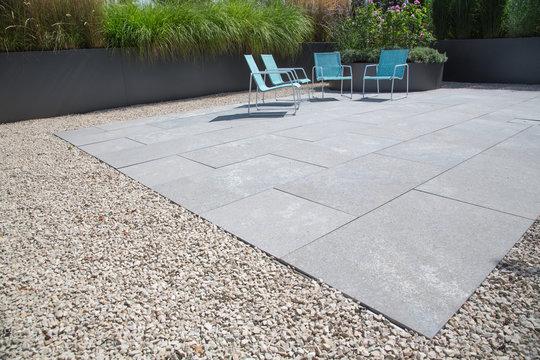 Moderne Garten- und Terrassengestaltung im Materialmix: Terrasse aus Steinplatten umgeben von Schotter und Metall Pflanzgefäßen mit Grünpflanzen