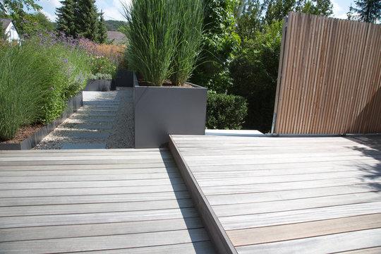 Moderne Garten- und Terrassengestaltung im Materialmix: Terrassen und Wand aus Holz , Gehweg aus Steinplatten umgeben von Schotter und mit Grünpflanzen bepflanzten Kübeln