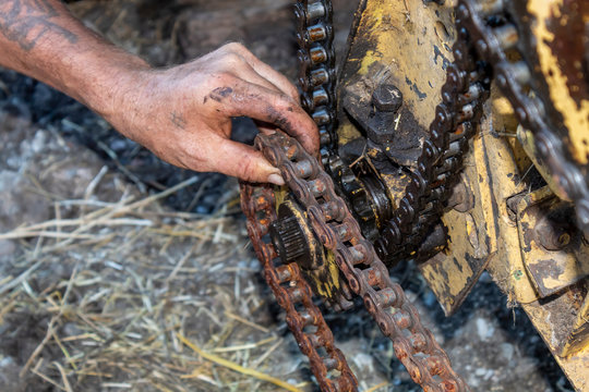 Man Hand Trying to Put Chain on Sprocket Wheel While Repairing Forage Harvester