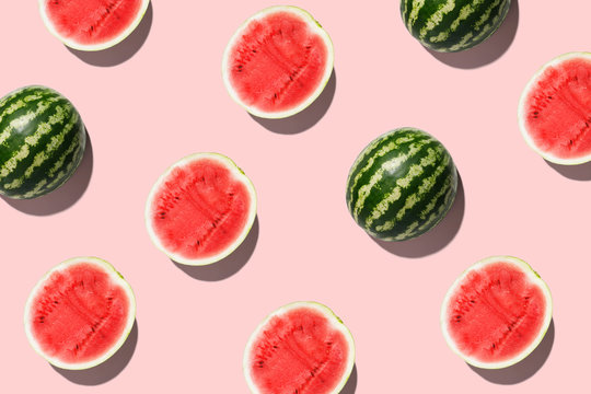 Pattern with ripe watermelon on pink background. Top View. Copy Space. Pop art design, creative summer concept. Half of watermelon in minimal flat lay style