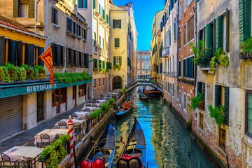 Foto auf Leinwand Gondeln Narrow canal with gondola and tables of restaurant in Venice, Italy. Architecture and landmark of Venice. Cozy cityscape of Venice.