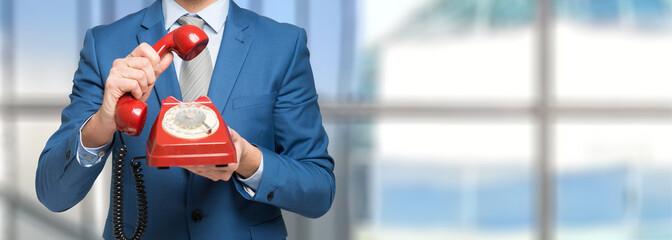 Businessman holding a vintage telephone