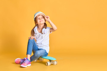 Stylish little girl child girl in casual with skateboard over yellow background.