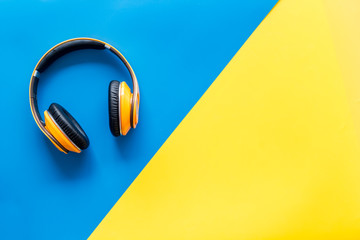 Wireless headphones as gadgets for listen to the music on yellow and blue background top view mock up