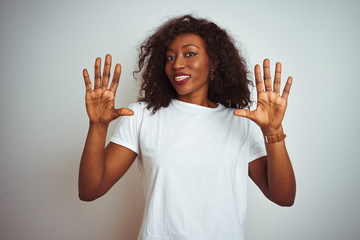 Young african american woman wearing t-shirt standing over isolated white background showing and pointing up with fingers number ten while smiling confident and happy.