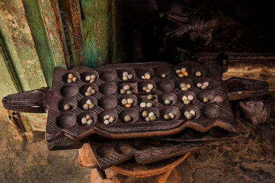 Hand playing Mancala game, Stone town, Tanzania. Mancala is a game which is very popular in Africa and Arabs