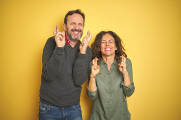 Beautiful middle age couple over isolated yellow background gesturing finger crossed smiling with...