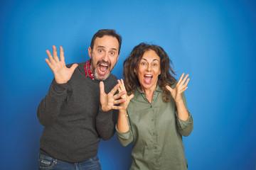 Beautiful middle age couple together standing over isolated blue background celebrating crazy and...