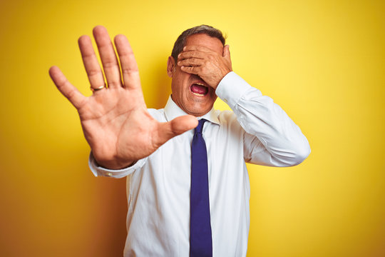 Handsome middle age businessman standing over isolated yellow background covering eyes with hands and doing stop gesture with sad and fear expression. Embarrassed and negative concept.