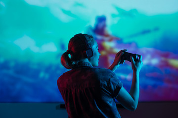 A gamer or a streamer girl at home in a dark room with a gamepad playing with friends on the networks in video games. A young man sits in front of a monitor