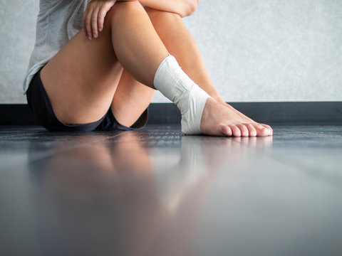 Injured athlete sitting on the sidelines due to ankle sprain