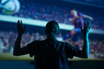 The girl is watching football, soccer in 3D, with glasses on the big screen. with entertainment and relaxation. action, rest in the cinema. Cheerleader, fan