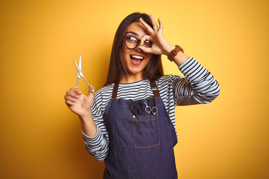 Young beautiful hairdresser woman holding scissors standing over isolated yellow background with happy face smiling doing ok sign with hand on eye looking through fingers