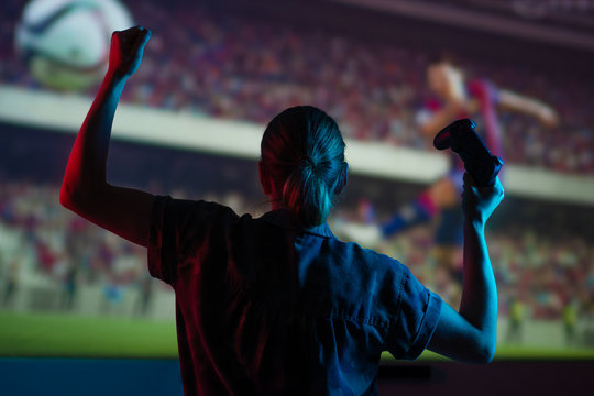 Soccer game, girl gamer playing a game in football headphones on a big screen, with bright light and a dark room. Gameplay, streaming, e-sports.