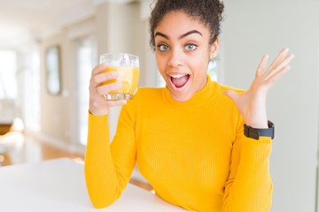 Poster Juice Young african american woman drinking a glass of fresh orange juice very happy and excited, winner expression celebrating victory screaming with big smile and raised hands