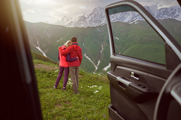Happy couple hugs on beautiful nature and mountains out of car