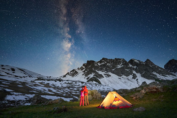 Couple standing near tent and looking at the milky way in mountains at night
