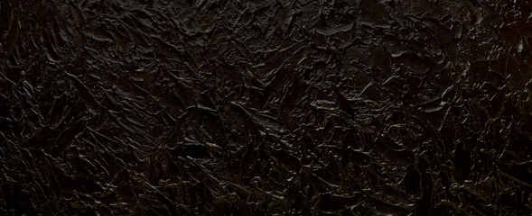Black texture background. Panorama in the form of a black textural background for design and decoration. Embossed texture of a wide format. Wall mural