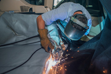 repair of the car interior. the man works with the welding in the trunk Wall mural