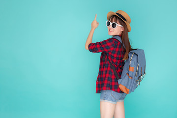 Back view beautiful portrait young asian woman wear hat and sunglasses smile excited enjoy travel summer trip in holiday isolated blue background, girl having backpack pointing something in vacation. Wall mural