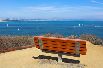 An empty bench sits overlooking San Diego bay on the Bayside Trail at Cabrillo National Monument in Point Loma, California.