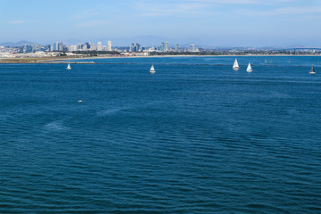 Boats sail in San Diego Bay with the city skyline in the background.
