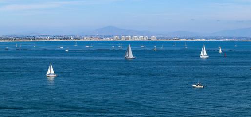 A panoramic view of the San Diego, California downtown skyline, the Coronado Bridge and the mountains.