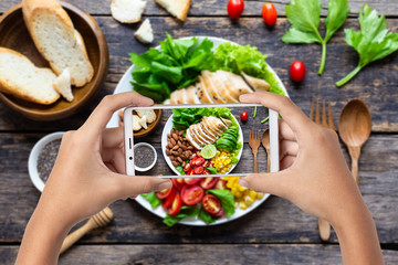 Hand hold smartphone woman takes photo healthy food for blog,photographer food Wall mural