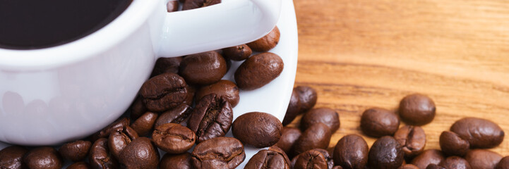 Coffee bean. On the background of wooden boards a cup of coffee and scattered coffee beans. Layout. Flat lay.