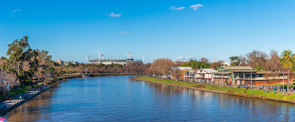 A large panorama of the Yarra River with the boathouses of Alexandra Gardens in the foreground and the Melbourne Cricket Ground in the distance